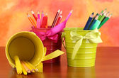 Colorful pencils and felt-tip pens in pails on color background — Stock Photo