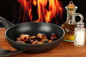 Roasted chestnuts in the pan and decanter with oil, salt and pepper on wooden table close-up — Stock Photo