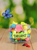Szklany wazon z papieru gwiazd z marzeń na drewnianym stole na naturalne tło — Zdjęcie stockowe