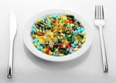 Bunte Kapseln und Pillen auf Teller mit Gabel und Messer, isoliert auf weiss — Stockfoto