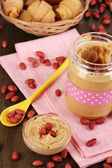 Delicious peanut butter in jar with baking on napkin on wooden table close-up — Stock Photo