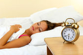 Young beautiful woman in bed and alarm clock — Stock Photo