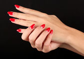 Beautiful female hands with red nails isolated on black — Stock Photo
