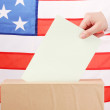 Hand with voting ballot and box on Flag of USA — Stock Photo #15509549