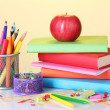 Composition of books, stationery and an apple on bright colorful background — Stock Photo #15510321