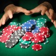 Poker chips and hands above it on green table — Stock Photo