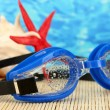 Blue swim goggles with drops on a bamboo pad, on blue sea background — Zdjęcie stockowe