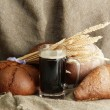 Tankard of kvass and rye breads with ears, on burlap background - Stock Photo