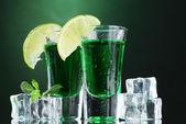 アブサン、ライム、緑色の背景上の氷の 2 つのメガネ — ストック写真
