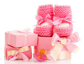 Pink baby boots, pacifier and gifts isolated on white — Stock Photo