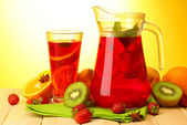 Sangria in jar and glass with fruits, on wooden table, on yellow background — Stock Photo