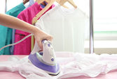 Woman hand ironing a shirt, on cloth background — Stock Photo