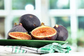 Ripe sweet figs on plate, on wooden table, on window background — Stock Photo