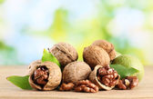 Walnuts with green leaves, on green background — Stock Photo