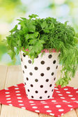 White pot with parsley and dill on wooden table on natural background — Stock Photo