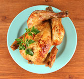 Roasted whole chicken on a blue plate on wooden background — Stock Photo