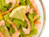 Salad with shrimps, lemon and lettuce leaves in bowl, isolated on white — Stock Photo