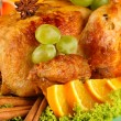 Stock Photo: Roastes chicken with grapes, lettuce and spices close-up. Thanksgiving Day