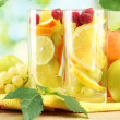 Glasses citrus fruits and raspberries, on green background — Stock Photo