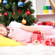 The little girl fell asleep with gift in their hands in festively decorated room - ストック写真