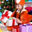 Little girl in suit of squirrels opens gift in festively decorated room - Stock Photo
