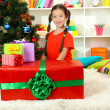 Little girl with large gift box near christmas tree — Stock Photo #15528759