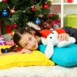 Little girl sleeping near christmas tree - Stockfoto