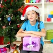 Little girl holding gift box near christmas tree - 图库照片