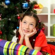 Little girl dreaming near christmas tree - Stockfoto