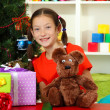 Little girl with large gift box near christmas tree — Stock Photo #15529101