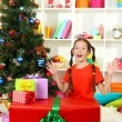 Little girl with large gift box near christmas tree — Stock Photo #15529143
