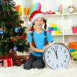 Little girl holding clock near christmas tree - Stockfoto