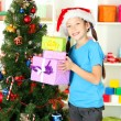 Little girl holding gift boxes near christmas tree — Stock Photo #15529261