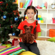 Little girl holding toy near christmas tree — Stock Photo #15529305