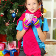 Little girl with pink scarf and cup of hot drink sitting near christmas tree — Stock Photo #15529307