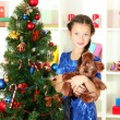 Little girl holding toy near christmas tree — Stock Photo #15529375