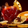 Fragrant mulled wine in glass with spices and oranges around on red background - 图库照片