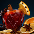 Fragrant mulled wine in glass with spices and oranges around on blue background — Stock Photo #15529549