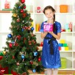 Little girl holding gift box near christmas tree — Stock Photo #15529575
