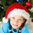 Little girl  sitting near christmas tree - Stock Photo