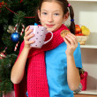 Little girl with pink scarf and cup of hot drink sitting near christmas tree — Stock Photo #15529599