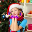 Little girl with pink scarf and multicolor gloves sitting near christmas tree — Stock Photo #15529617