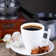 White cup of Turkish coffee with coffee maker and coffee mill on wooden table - Stockfoto