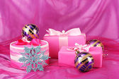Beautiful gifts, Christmas balls and snowflake on a pink background — Stock Photo
