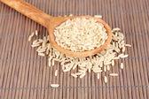 Reis in holzlöffel auf bambusmatte — Stockfoto