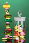 Capsules and pills hill and in receptacle on green background — Stock Photo