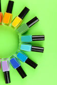 Group of bright nail polishes, on green background — Stock Photo
