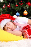 The little girl fell asleep with gift in their hands in festively decorated room — Stockfoto