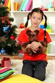 Little girl holding toy near christmas tree — Stock Photo