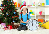 Little girl holding clock near christmas tree — Foto de Stock